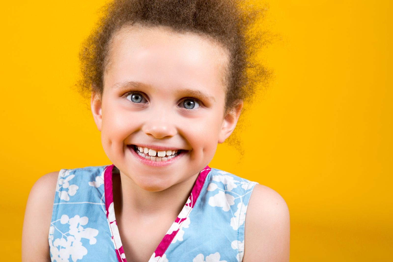 Girl in blue dress on bright yellow backdrop