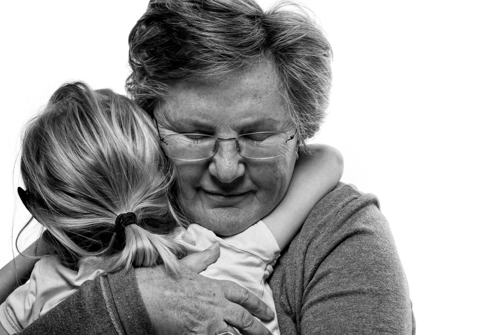 Grandmother hugging her granddaughter, black and white studios photograph with emotion