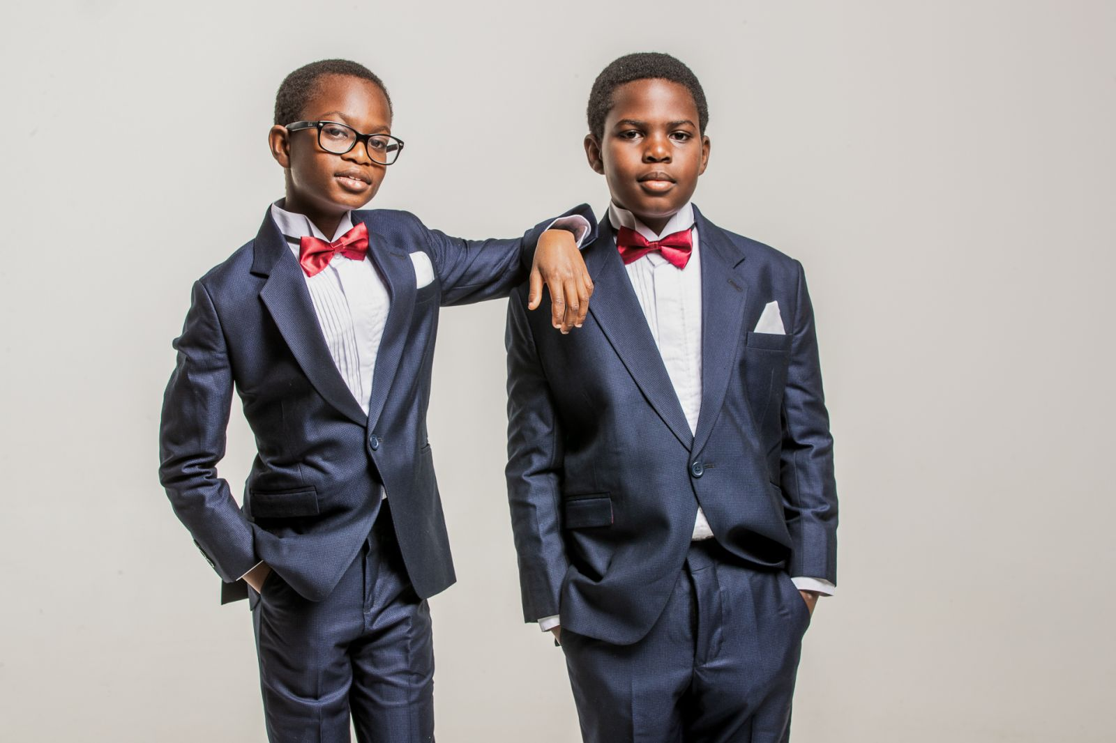 Portrait of 2 young brothers wearing suits and bow ties