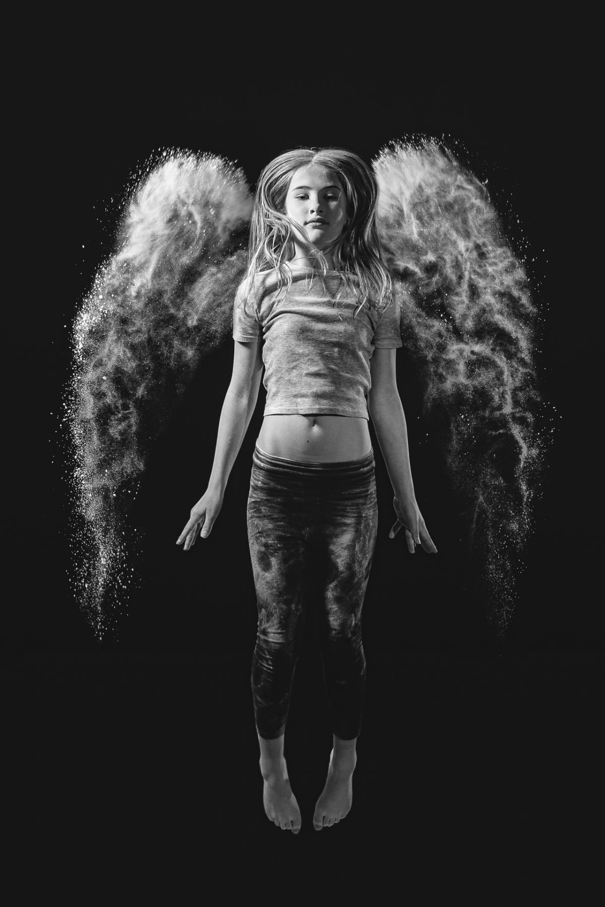 Girl seemingly floating with angel wings made out of flour