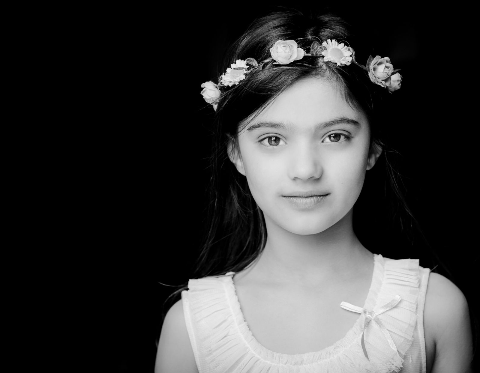 Black and white portrait of girl with flowers in hair