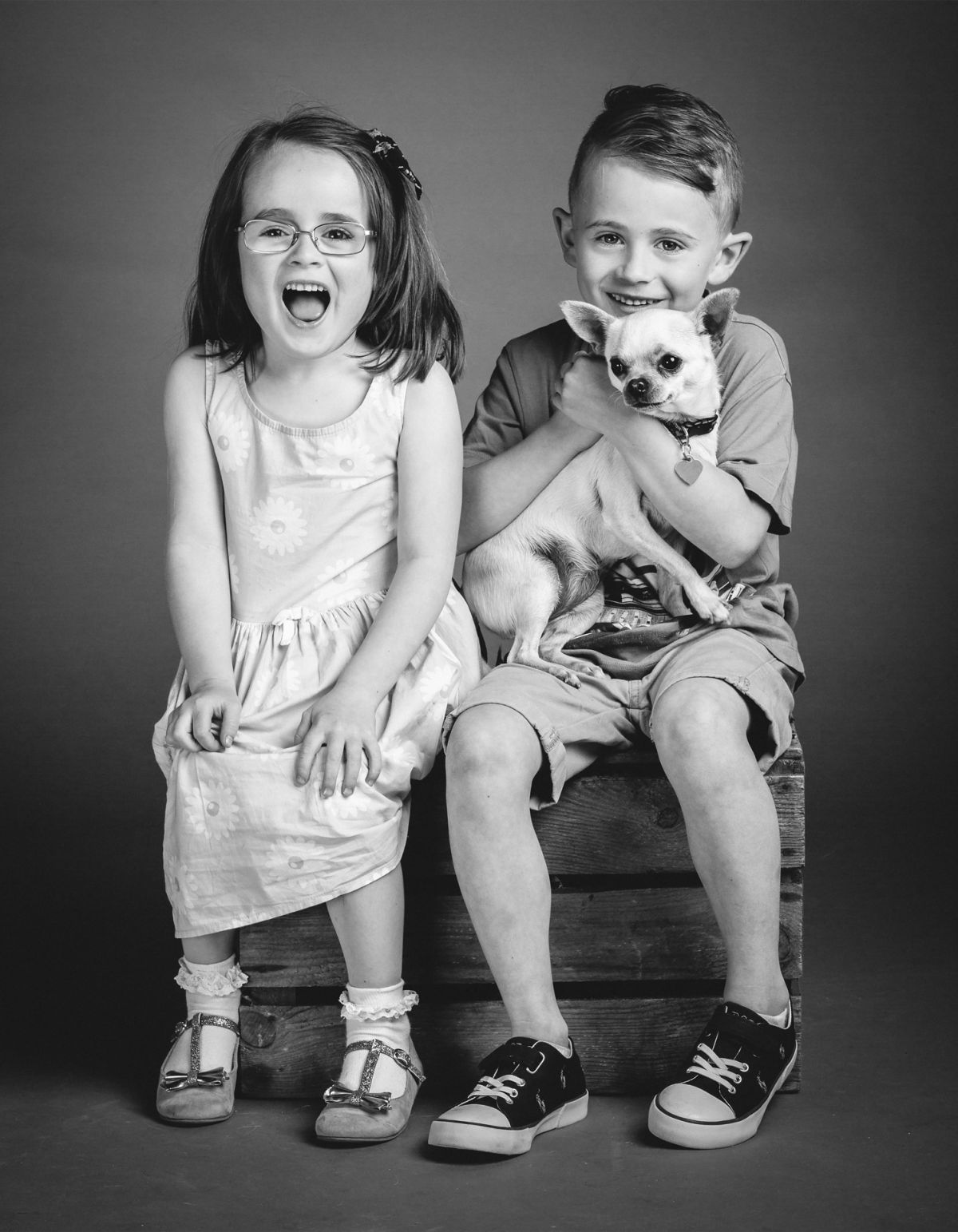 Boy and Girl sitting on a box holding a small dog
