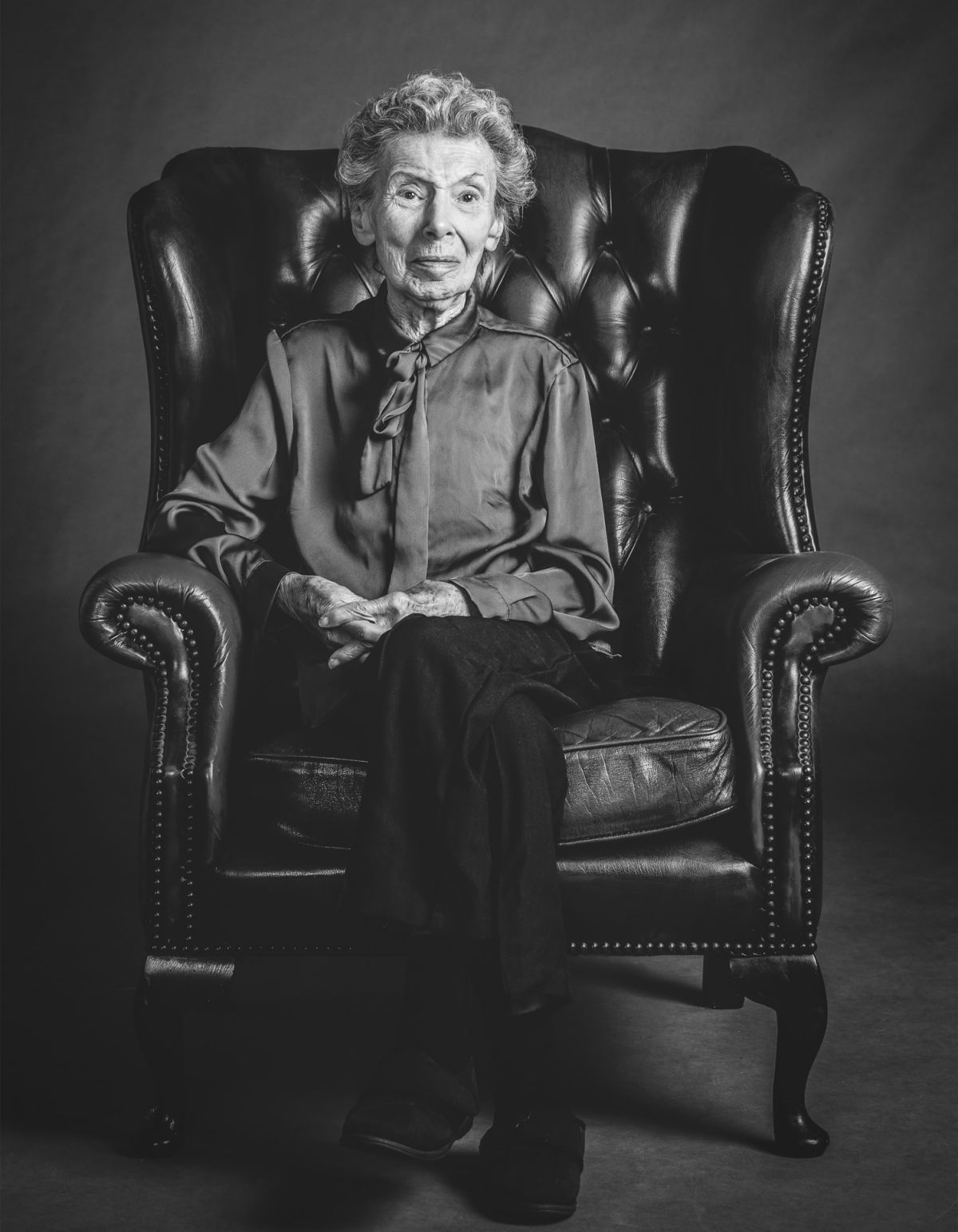 Elegant Portrait of Elderly Woman sitting in Chesterfield chair