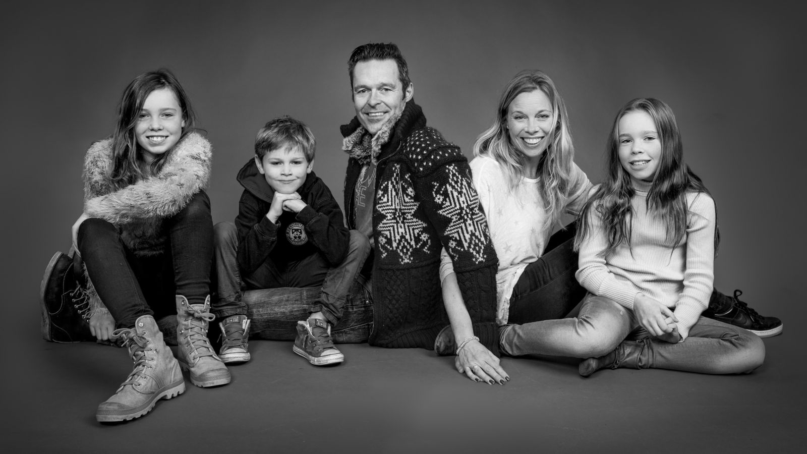 Studio family portrait with 3 children sitting on the floor with grey background