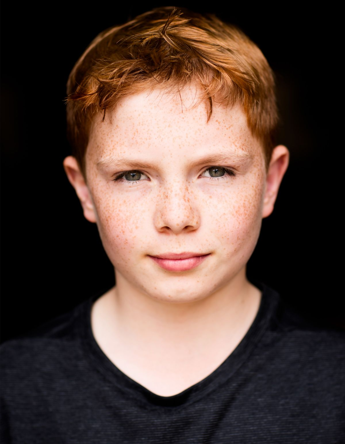 Young boys head shot photo with freckles, ginger hair and black background