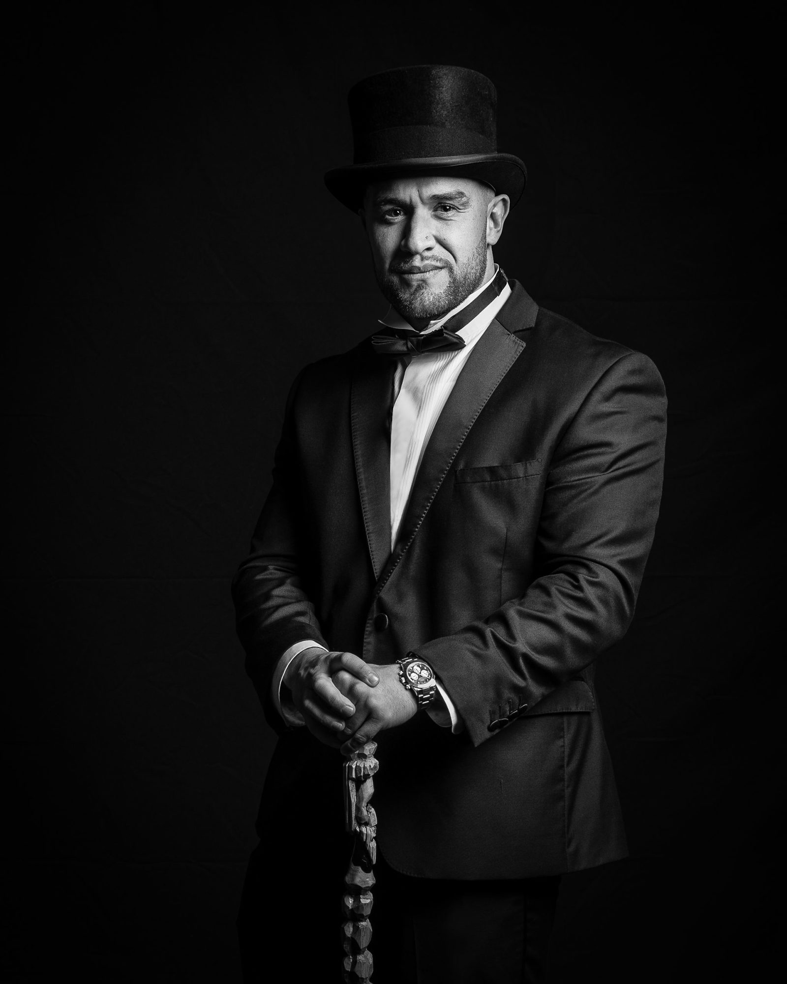 Elegantly dressed man with black tie, top hat and a cane